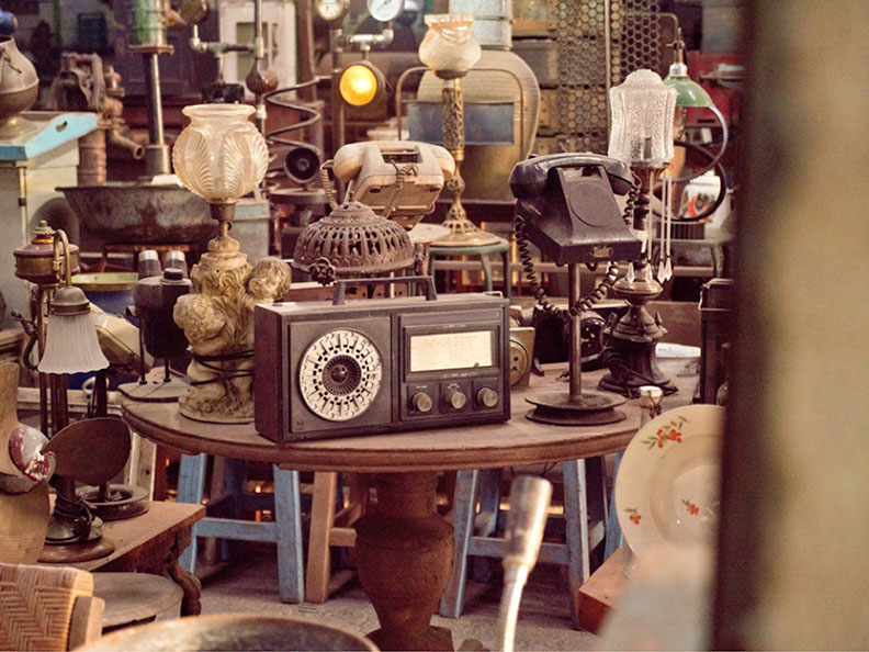 old radio on a table with other antiques in the background