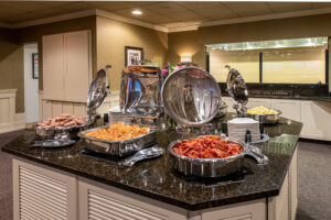 complimentary breakfast buffet area with sausage, waffles, and bacon