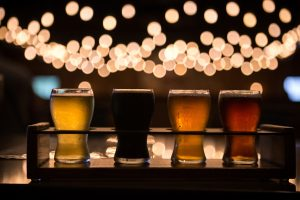 a flight of several different beers with blurred lights in the background